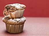 Two chocolate muffins with icing sugar, one partly eaten