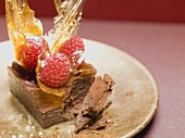 Small chocolate cake with raspberries & caramel fans, partly eaten