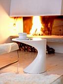 Designer-Beistelltisch in Wohnzimmer vor offenem Kamin