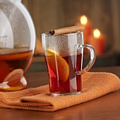 Hot punch in glass with cinnamon stick