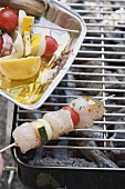 Raw fish & vegetable kebabs on barbecue rack & in aluminium dish