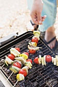 Woman grilling fish and vegetable kebabs out of doors