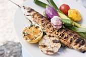 Grilled fish (Steckerlfisch) with vegetables and lemon