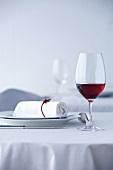 Glas Rotwein auf weiss gedecktem Tisch