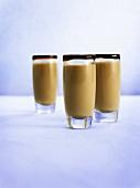 Drei Gläser Baileys mit Schokoladensauce am Glasrand