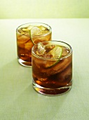 Two glasses of rum and cola with lime slices and ice cubes