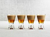 Vier Drinks mit Amarula und Ahornsirup in Schnapsgläsern
