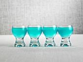 Vier Schnapsgläser mit blauen Alkopops