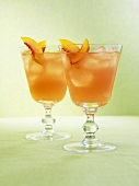 Two drinks with ice cubes and fresh peach slices