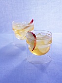 Two Drambuie cocktails with slices of apple and ice cubes