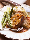 Bacon-wrapped meatloaf with tomato sauce, asparagus, mashed potato