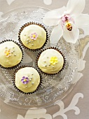 Vanilla cupcakes decorated with sugar flowers