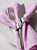Fabric napkin with napkin ring and cutlery on plate