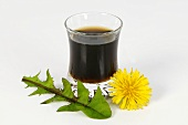 A glass of dandelion juice with flower and leaf