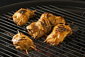 Stuffed, marinated chicken breasts on a barbecue