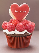 Chocolate cupcake with raspberries & heart-shaped biscuit
