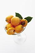 Several ripe medlars in a glass