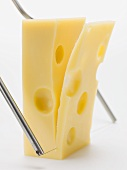 Cutting a slice of Emmental cheese