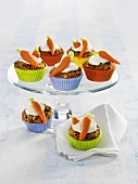 Carrot muffins in coloured paper cases on glass cake stand