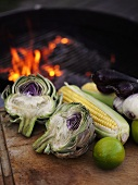Vegetables, corn on the cob & limes beside charcoal barbecue