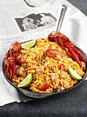 Paella in frying pan on a newspaper