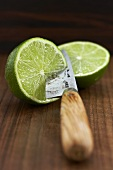Two lime halves with knife
