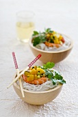 Two bowls of prawn and mango salad with rice noodles