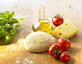 Still life with pizza dough, tomatoes, cheese, olive oil, basil