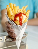 Hand holding a cone of chips with ketchup and mayonnaise