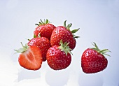 Several whole strawberries and half a strawberry