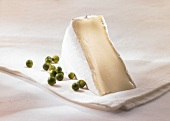 A piece of Brie with green pepper