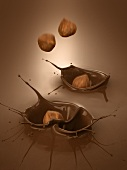 Hazelnuts falling into melted chocolate