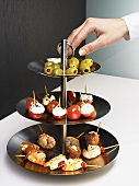 Hand reaching for olives on tiered stand with appetisers