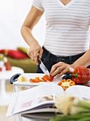 Frau schneidet Paprikaschote in Küche