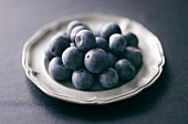 Several blueberries on pewter plate