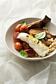 Fried fish fillet with tomatoes, beans and aubergines
