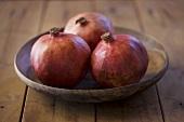 Three pomegranates in a wooden dish