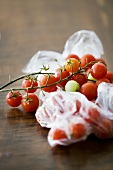 Tomatoes on the vine, some in plastic bag