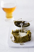 Stuffed Camembert wrapped in vine leaves, glass of beer