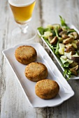 Fish cakes, potato salad and glass of beer