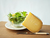 A piece of Gouda cheese with rocket salad in background