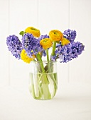 Ranunculus and hyacinths in glass vase