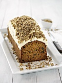 Carrot cake with cream topping and chopped nuts