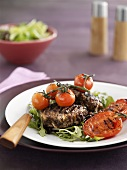 Grilled burgers on rocket with grilled tomatoes