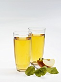 Two glasses of apple juice, wedge of apple and leaves