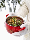 Hands holding pot of cassoulet