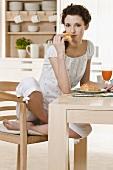 Junge Frau isst Croissant zum Frühstück