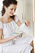 Young woman pouring milk over cornflakes