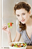Young woman eating Greek salad