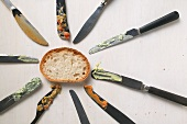 Knives with the remains of spreads and a slice of bread